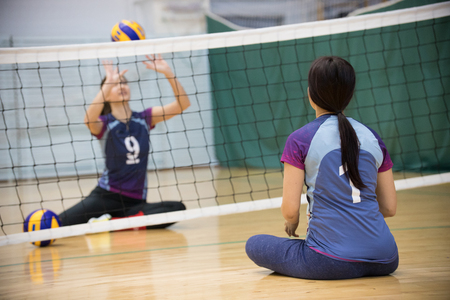 Foto de Sports for disabled people. Training. Two young women sitting on the floor and playing volleyball. - Imagen libre de derechos