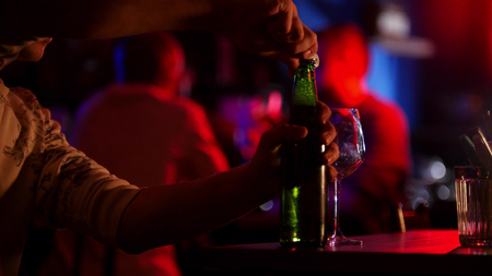 Photo pour Bar with neon lighting. A man opens up a beer bottle - image libre de droit