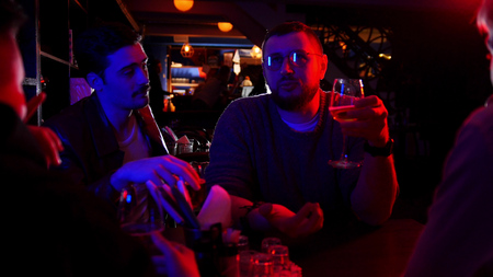 Photo pour Bar with neon lighting. Group of friends sitting by the table and drinking alcohol while talking - image libre de droit