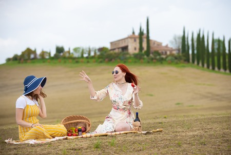 Photo pour Two women sitting on the blanket having a picnic, talking and eating fruits - image libre de droit