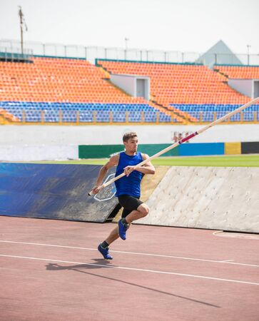 Foto per Pole vault - a young man runs up holding a pole in stadium - Immagine Royalty Free