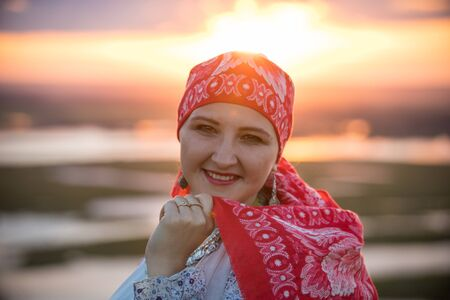 Photo pour An adult smiling woman in traditional folk clothes on a background of the sunset - image libre de droit