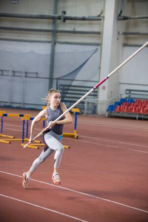 Foto per Pole vaulting indoors - young woman in leggins running with a pole in the hands - Immagine Royalty Free