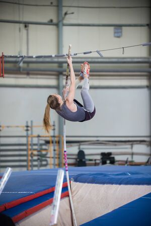 Foto per Pole vaulting - young woman is jumping over the high bar - Immagine Royalty Free