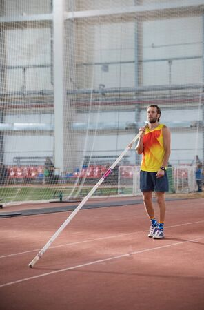 Foto per Pole vaulting - man with a beard is standing with a pole - Immagine Royalty Free