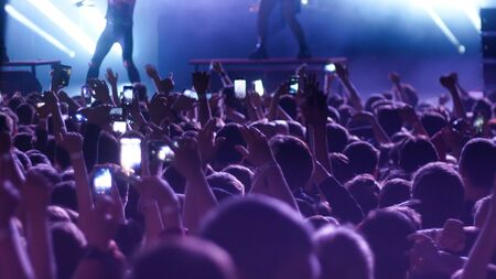 Photo pour Energetic people dancing with their hands up at the concert. Mid shot - image libre de droit
