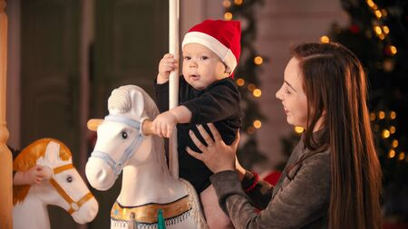 Photo for Christmas decorated studio - A smiling young mother standing near by her baby on carousel - Royalty Free Image