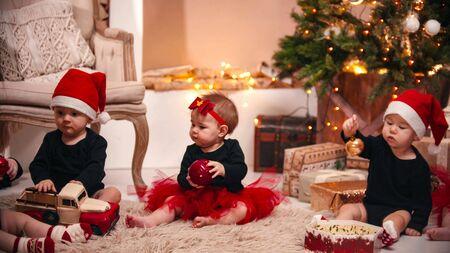 Foto de Christmas decorations in the studio - little babies playing with christmas toys - Imagen libre de derechos