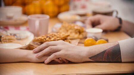 Foto de A cute couple holding hands in the cafe. Mid shot - Imagen libre de derechos