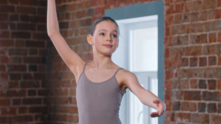 Photo for A little pretty ballerina girl training movements in the studio - Royalty Free Image