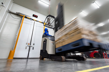 Photo pour Worker Stand-on stacker truck used to lift and move the ready meals goods stock in cold room or freezer room. - image libre de droit