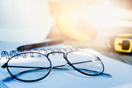 Photo pour Engineers placed the spectacles on diary after work with sunlight. Go to relaxing in the weekend activity concept. - image libre de droit