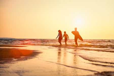Photo for Silhouette of Young surfers with brethren they're relaxing on sunset beach. Summer activity of people on the beach concept. Extreme sports concept. - Royalty Free Image