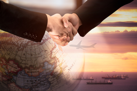 Foto de Businessman handshake for agreement of logistics partners with Double Exposure Image of Globe World Map and shipping. - Imagen libre de derechos