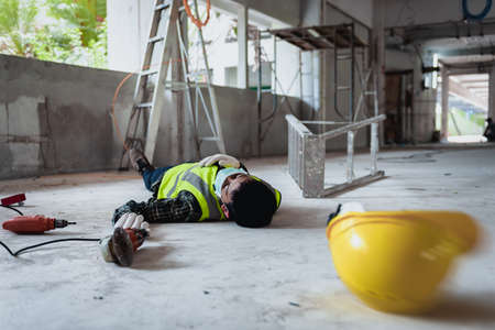 Foto de Work accidents of worker in the workplace at construction site area, Builder accident falls ladder on floor and Unconscious, Electric suction, Unsafe concept. Add zoom filter effect for feelings. - Imagen libre de derechos