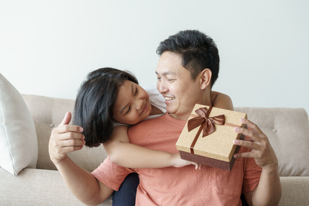 Photo for asian father giving gift box for daughter  in the living room. Cute girl and father sitting on sofa be happy  in home - Royalty Free Image