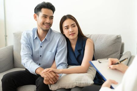 Photo for Asian couple join hand to encourage while sitting on the couch in the psychiatrist room to consult mental health problems by doctor, Health and illness concepts - Royalty Free Image