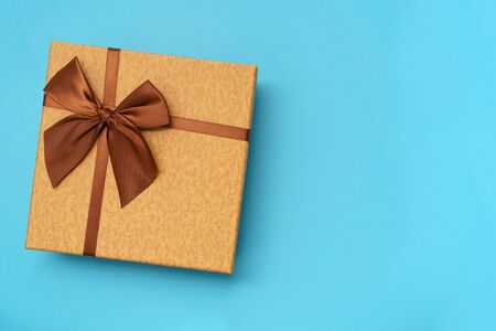 Photo for Brown gift box with brown  ribbon isolated on blue background - Royalty Free Image