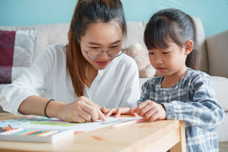 Photo for Asian family with mother and daughter doing together activities at home. happy mom and child doing learning and drawing on table in the living room in the morning - Royalty Free Image