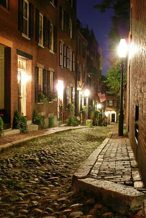 night time image of an old 19th Century cobble stone road in Boston Massachusetts, lit only by the gas lamps revealing the shuttered windows and brightly lit doorways of the rowhouses on Acorn Street