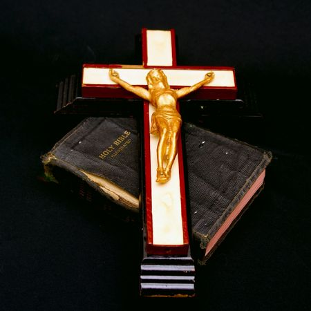 full color image of an old crucifix laying on top of an ancient leatherbound bible