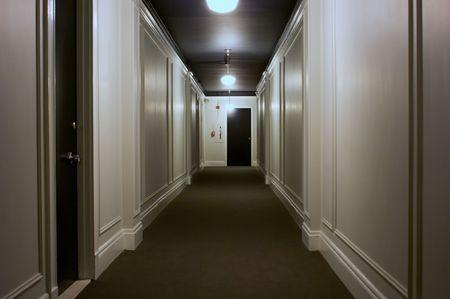 long interior hallway showing doors, lights, ceiling, carpet