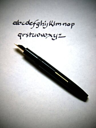 alphabet being written in calligraphy on parchment paper with pen