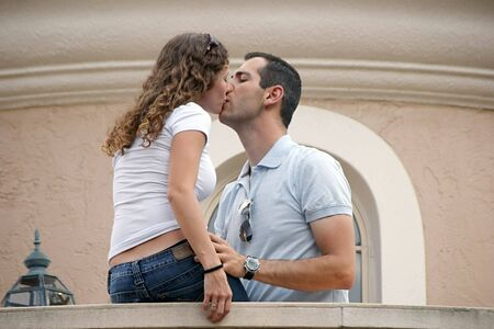 attractive young couple kissings on balcony, woman is sitting man is standing. shot on overcast day providing soft lighting