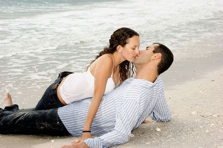 A young american couple are on the beach kissing, the woman is on top of the man