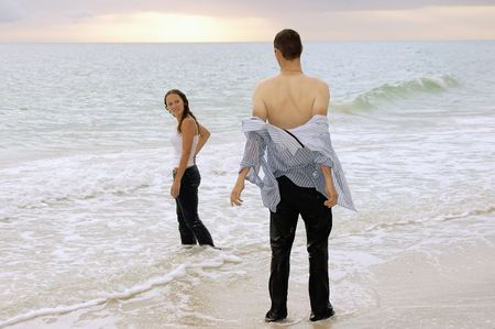 a soaked fully clothed couple are at the water's edge at the beach, the man is taking off his shirt.
