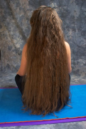 back view of a woman with long messy hair down to her waist and looking like there are dreadlocks.