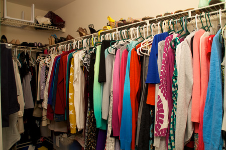 closet belonging to a woman. Full of clothing, hangers, shelves and shoes.