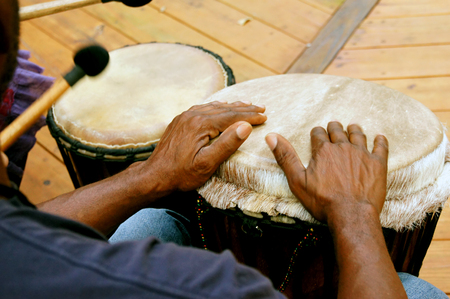 Looking over a man's shoulders as he drums in a drum circle.