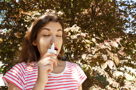 Young beautiful woman using nose spray in the park.