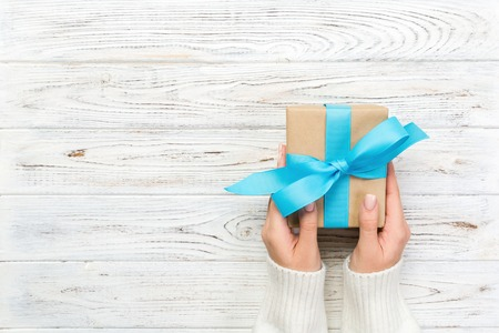 Foto de Woman hands give wrapped valentine or other holiday handmade present in paper with blue ribbon. Present box, decoration of gift on white wooden table, top view with copy space. - Imagen libre de derechos