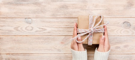 Foto de Woman hands give wrapped valentine or other holiday handmade present in paper with blue ribbon. Present box, decoration of gift on white wooden table, Top view banner with copy space for you design. - Imagen libre de derechos