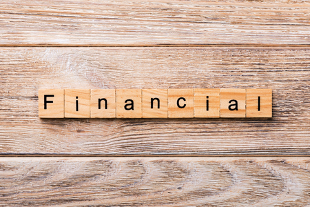 financial word written on wood block. financial text on wooden table for your desing, concept.