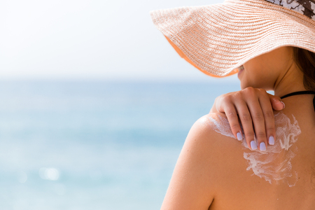 Photo pour Sunscreen sunblock. Woman in a hat putting solar cream on shoulder outdoors under sunshine on beautiful summer day. - image libre de droit