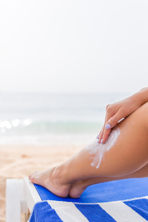 Photo pour Young woman is having rest at the beach and protects her skin applying sunblock on her leg. - image libre de droit
