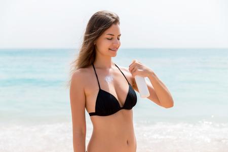 Foto de Smiling woman is applying sun cream from the spray on her body at the sea background. - Imagen libre de derechos