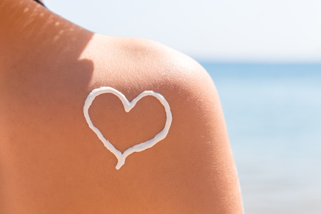Photo pour Heart made of sun cream is drawn on woman's shoulder at the beach. - image libre de droit