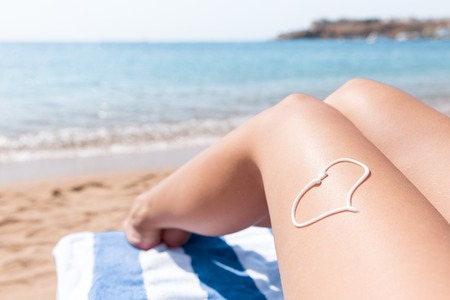 Photo for Sunscreen in the form of heart on woman's leg sunbathing on the towel by the sea. - Royalty Free Image