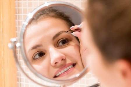 Photo for Beautiful woman with tweezers is plucking eyebrows while looking into the mirror in bathroom. Beauty skincare and wellness morning concept. - Royalty Free Image