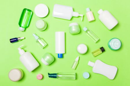 Group of plastic bodycare bottle Flat lay composition with cosmetic products on green background empty space for   design. Set of White Cosmetic containers, top view with copy space.
