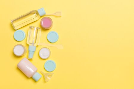 Top view composition of small travelling bottles and jars for cosmetic products on yellow background. Facial skin care concept with copy space for your design.