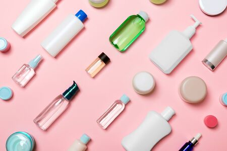 Top view of different cosmetic bottles and container for cosmetics on pink background. Flat lay composition with copy space.