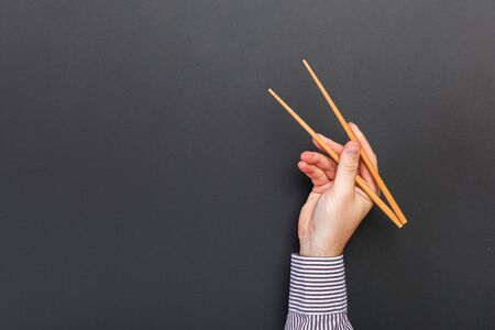 Foto de Creative image of wooden chopsticks in male hands on black background. Japanese and chinese food with copy space. - Imagen libre de derechos
