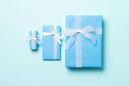 wrapped Christmas or other holiday handmade present in paper with white ribbon on blue background. Present box, decoration of gift on colored table, top view.