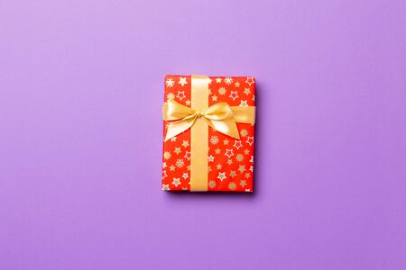 Photo for Gift box with gold bow for Christmas or New Year day on purple background, top view with copy space. - Royalty Free Image