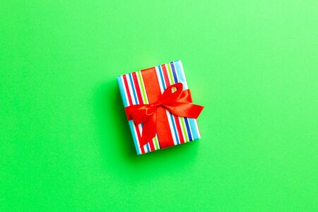 wrapped Christmas or other holiday handmade present in paper with red ribbon on green background. Present box, decoration of gift on colored table, top view with copy space.